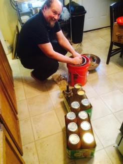photo of me helping to decant six gallons of fire cider.