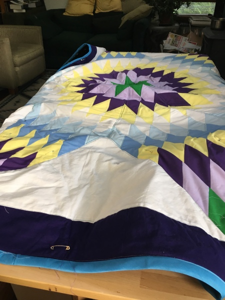 a big quilt in a lone star pattern made up of numerous diamond shapes radiating from the center — in purple, white, blue and yellow, with a backing of galaxies and planets