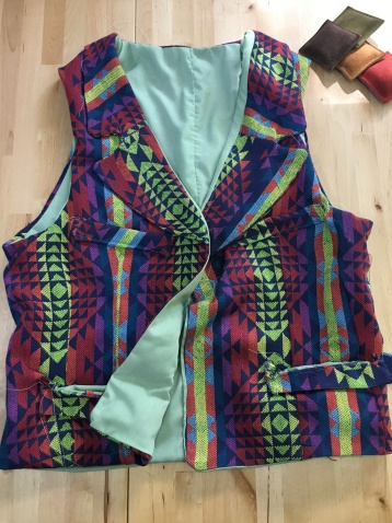 A vest in jewel tones and geometric patterns, with a sea-green lining