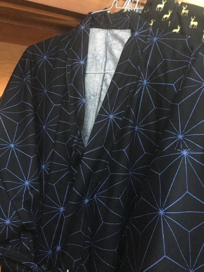 A Japanese style robe in black with a blue star geometric pattern
