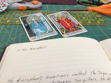 Tarot cards Hierophant and High priestess with an open book nearby