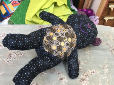 stuffed bear of purple & gold accents with star-themed main fabric
