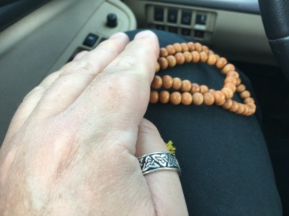 Hands holding prayer beads well seated in the car.